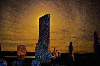 Lewis' Callanish stones set against a golden backdrop from the night sky.