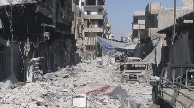 Destroyed buildings and vehicles in the deserted streets of Raqqa.