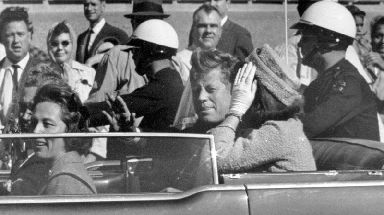 President John F. Kennedy waves from his car with First Lady Jacqueline Kennedy in a motorcade in Dallas.