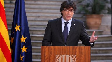 Carles Puigdemont stood beside the EU and Catalan flags for his televised address.
