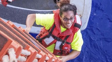 Tasha Fuiaba climbs aboard the USS Ashland after being rescued.