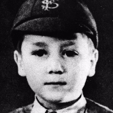 A young John Lenon wearing a Strawberry Fields hat.