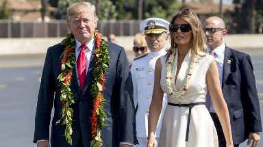 President Donald Trump and first lady Melania Trump wear leis as they arrive at Joint Base Pearl Harbor Hickam, Hawaii.