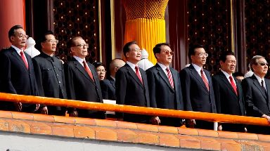 Chinese leaders stand for the national anthem.