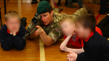 Weapon: A Royal Marine commando shows an unloaded weapon to primary school pupils.