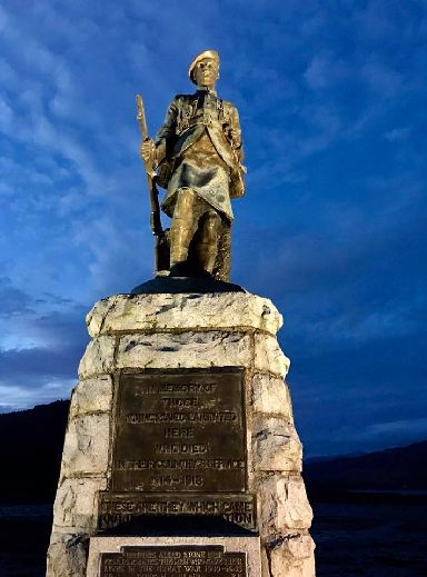 Inveraray's war memorial against a bright blue evening sky.