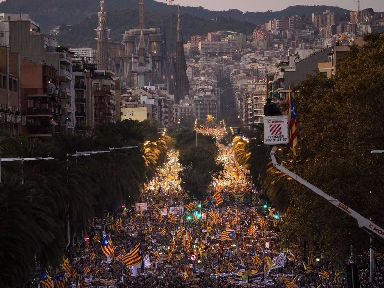 Demonstrators march in Barcelona backdropped by the Sagrada Familia church.
