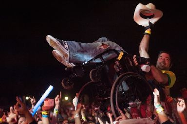 A fan crowd surfs in his wheelchair at Slayer.