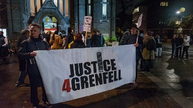 Marchers with posters and banners on the monthly slow and silent walk to demand justice for the victims of Grenfell.