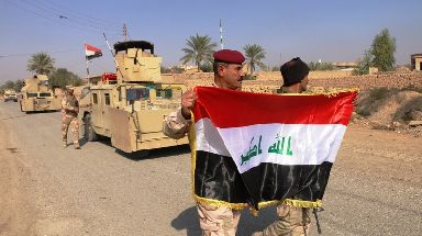 Troops raised the Iraqi flag in territory liberated from IS near Rawa.