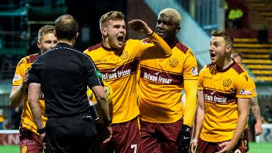 Chris Cadden and his teammates complain to the referee when the penalty is awarded against Motherwell.