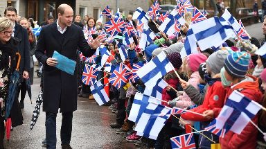 Schoolchildren greet Prince William as he arrives at auttasaari Comprehensive School in Helsinki.