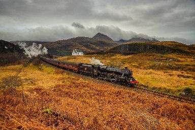 The Jacobite steam train ploughs through the countryside.