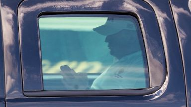 Donald Trump uses his phone inside an armoured presidential vehicle.