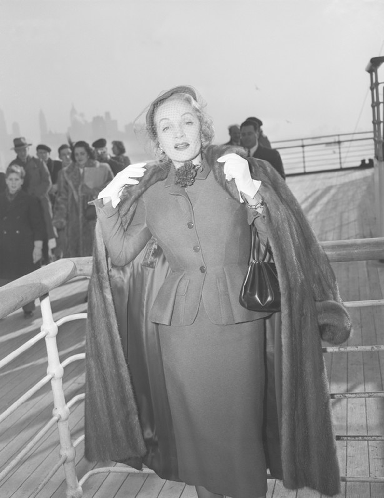 Marlene Dietrich: Wearing a Christian Dior day suit on-board the Queen Elizabeth arriving in New York in 1950.