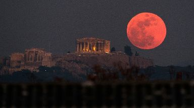 A super blue blood moon rises behind the 2,500-year-old Parthenon temple in Greece.