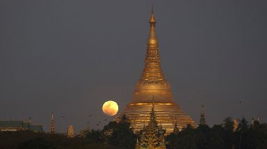 The moon rises behind Myanmar landmark Shwedagon pagoda.