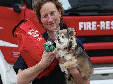 A fire officer demonstrates a pet sized oxygen mask on a dog