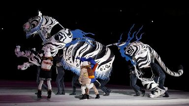 On stage children hurried after a giant White Tiger