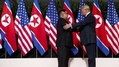 Kim Jong-un and Donald Trump share a historic handshake.