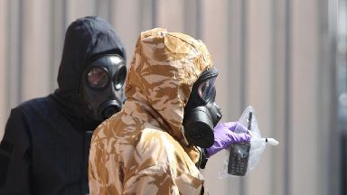 Investigators in chemical suits remove an item as they work behind screens erected in Rollestone Street, Salisbury