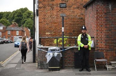 A police officer stands beside a sealed off bin