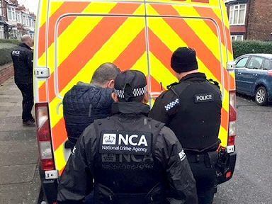 Officers during a raid in a major operation aimed at tackling people smuggling