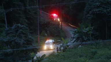 Two ambulances with flashing lights leaves the cave rescue area on Monday