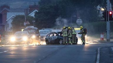 Firefighters deal with a burnt out car in the Cherryhill area of Dundonald