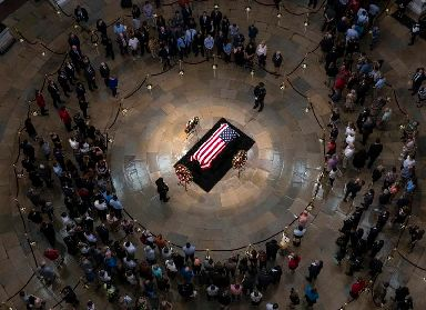 Tributes: Members of the public walk past the flag-draped coffin of John McCain.