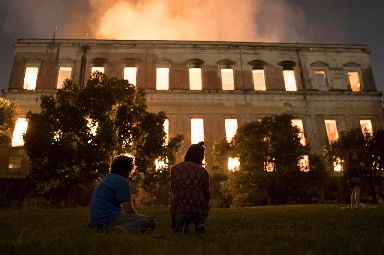 People watch as flames engulf the 200-year-old National Museum of Brazil