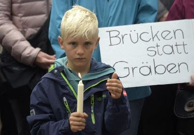 A boy holds candles as he stands in front of a poster promoting democracy over extremism in Chemnitz.