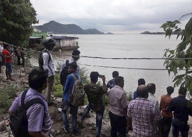 Passersby standing on the opposite bank watch rescuers search the waters of the Brahmaputra River.