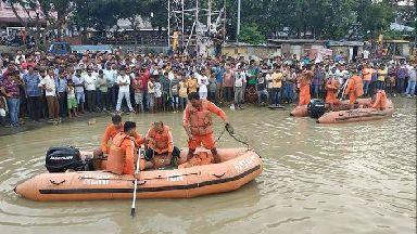 People watch rescuers search the waters of the Brahmaputra River.