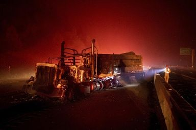 A scorched logging truck rests on the road after becoming caught in the Delta Fire