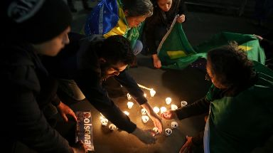 People light candles in support of Jair Bolsonaro.