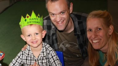 Dr Sam Williams and Katy Williams pictured with Finn who is wearing a happy birthday crown.