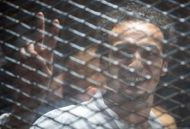 Mahmoud Abu Zaid smiles inside a cage in the Cairo court