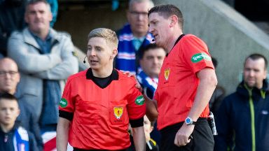 Referee Craig Thomson checks the back of Calum Spence's head.