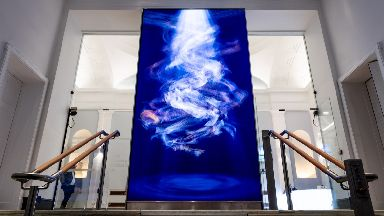 Entrance: Floor-to-ceiling video wall exhibiting digital art.