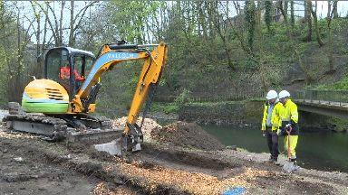 Digger: Work has begun along the popular Glasgow riverbank.