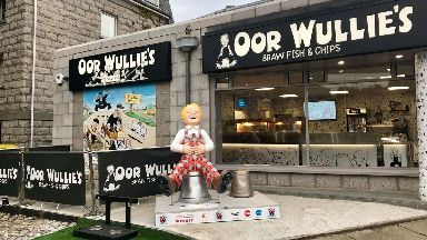 One of the statues has been placed outside the Oor Wullie chip shop in Aberdeen.