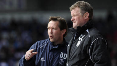 Dundee's football management team of Gordon Chisholm and Billy Dodds are the first to leave Dens Park on a day of cuts.