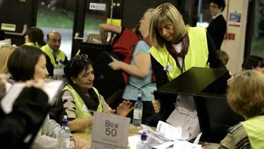 Count: Election workers sift through the ballots.