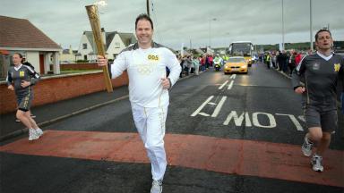 STV News anchor John MacKay carries the Olympic Torch in Stranraer, June 8 2012