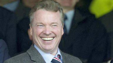 Quality photo of Craig Whyte, Rangers oldco owner, smiling during game at Ibrox.