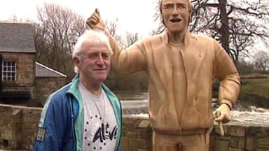 Sir Jimmy Savile with the statue of himself that was unveiled in Glasgow in 1993.