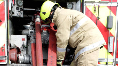Fireman with hose at engine. Quality generic photo