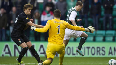 Hibernian striker Leigh Griffiths (right) rounds goalkeeper Fraser Forster to open the scoring for the home side