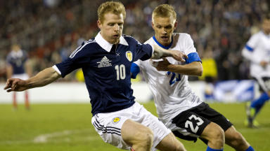 Scotland's Chris Burke (left) is closed down by Taijo Teniste.